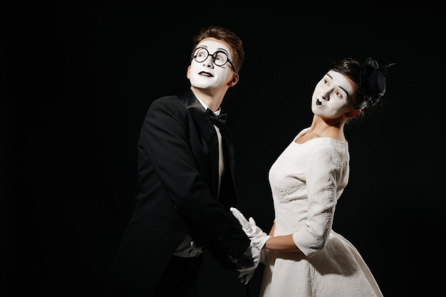 Portrait of couple mime on black background. man in tuxedo and glasses and woman in white dress Premium Photo