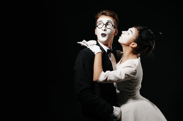 Portrait of couple mime on black background. woman in white dress kissing man in tuxedo and glasses Premium Photo
