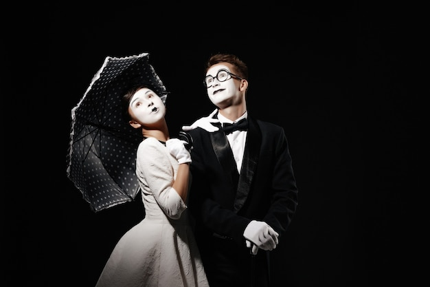 Portrait of couple mime with umbrella on black background. man in tuxedo and glasses and woman in white dress. space for text Premium Photo