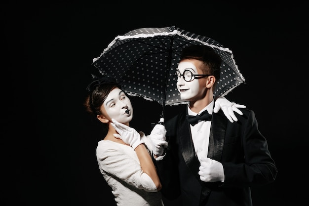 Portrait of couple mime with umbrella on black background. man in tuxedo and glasses and woman in white dress Premium Photo