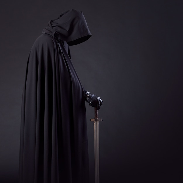Portrait of a courageous warrior wanderer in a black cloak and sword in hand. Premium Photo