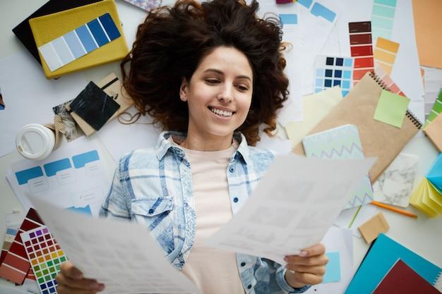 Portrait of creative young woman holding photographs Premium Photo