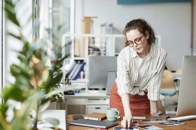 Portrait of creative young woman reviewing photographs while working on editing and publishing in modern office, copy space Premium Photo