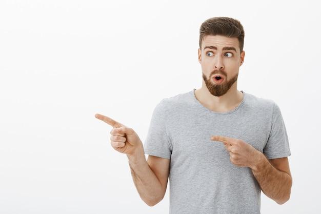 Ritratto di un affascinante modello maschio curioso e stupito di bell'aspetto con la barba che tiene il respiro che piega le labbra in un suono wow che guarda e punta a sinistra verso l'acconciatura fresca che vuole lo stesso mentre si trova nel negozio di barbiere Foto Gratuite