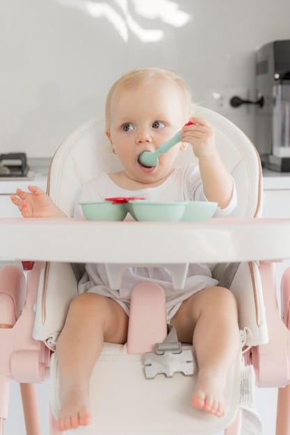 Portrait of cute baby girl eating food Free Photo