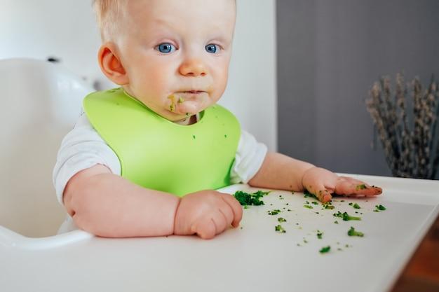 Ritratto di bambina carina seduta disordinata dopo l'alimentazione Foto Gratuite