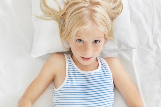 Portrait of cute blonde girl wearing sailor t-shirt, looking surprisedly, awaking in morning hearing loud alarm cloak. adorable girl feeling comfort while resting in bed in her room Free Photo