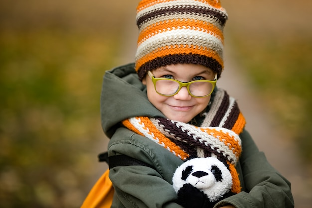 The portrait of cute boy in the glasses and warm knitting hat and scarf with his toy panda in the autumn park Premium Photo