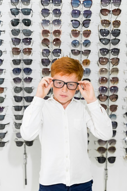 Portrait of cute boy wearing spectacle standing against eyeglasses rack in optics shop Free Photo