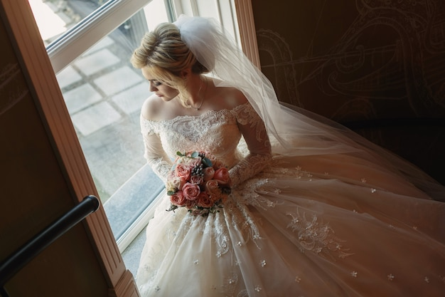 Portrait of cute bride with bridal bouquet of pink roses indoor. pretty happy bride in luxury dress and long veil near the window. young  bride with a beautiful neckline holding bouquet of flowers. Premium Photo
