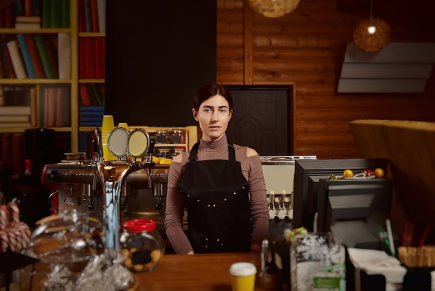 Portrait of a cute brunette woman barista in apron standing behind the bar Premium Photo