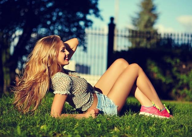 Ritratto di carino divertente sexy giovane elegante sorridente donna ragazza modello in panno moderno luminoso con perfetto corpo abbronzato all'aperto che giace nel parco in pantaloncini jeans tenendo in mano capelli forti e sani Foto Gratuite
