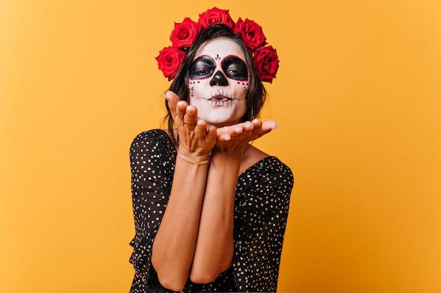Ritratto di ragazza carina con corona di rose rosse, che celebra halloween. la modella in abito nero sta inviando un bacio d'aria Foto Gratuite