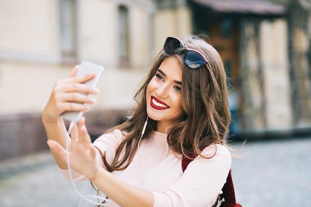 Ritratto di ragazza carina con capelli lunghi e labbra vinose che fanno selfie sulla strada in città. indossa una camicia bianca, sorridendo. Foto Gratuite
