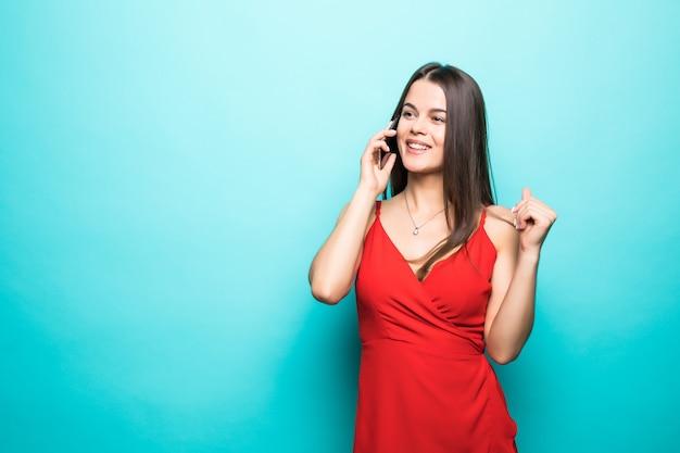Ritratto di una ragazza carina felice in abito parlando al cellulare e ridendo isolato sopra la parete blu Foto Gratuite