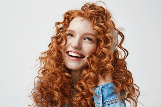 Portrait of cute happy girl smiling touching her curly red hair . Free Photo