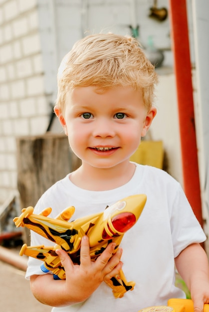 Portrait of cute happy little blond boy holding plane and car toys. adorable child walking in park on sunny day. Premium Photo