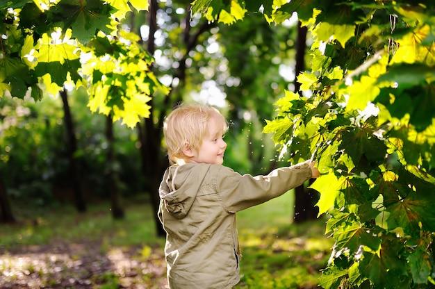 Portrait of cute happy little boy having fun in summer park after rain Premium Photo