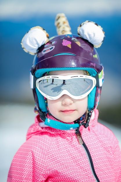 Portrait of cute happy skier girl in helmet and goggles in a winter ski resort Premium Photo