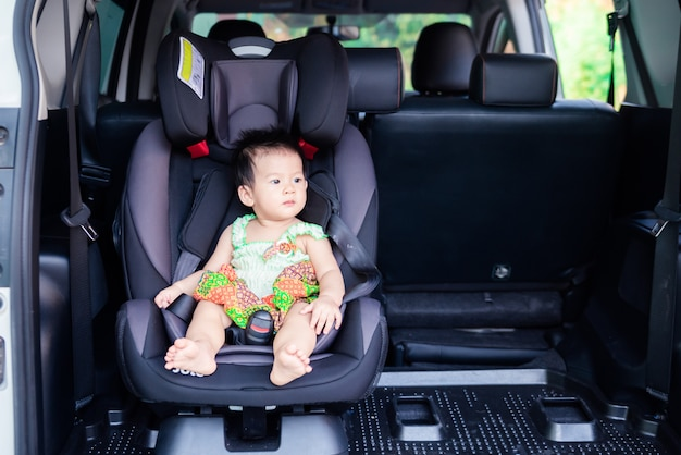 Portrait of cute little baby child sitting in car seat. child transportation safety Premium Photo