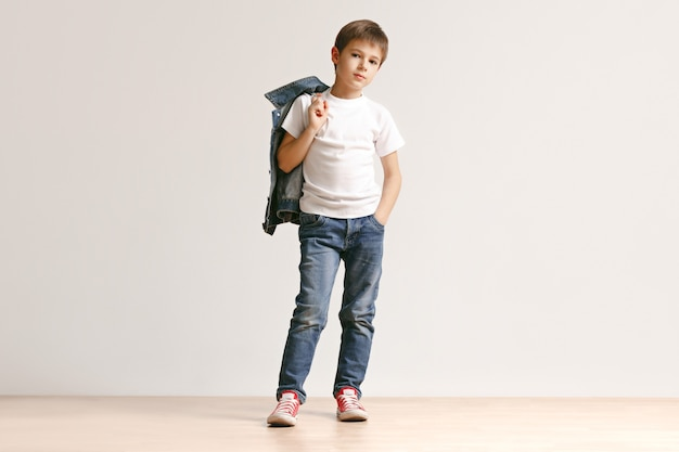 The portrait of cute little boy in stylish jeans clothes looking at camera at studio Free Photo