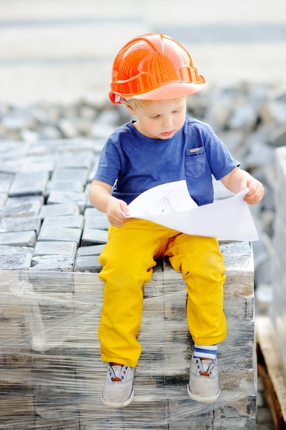Portrait of cute little builder in hardhats reading construction drawing outdoors. Premium Photo