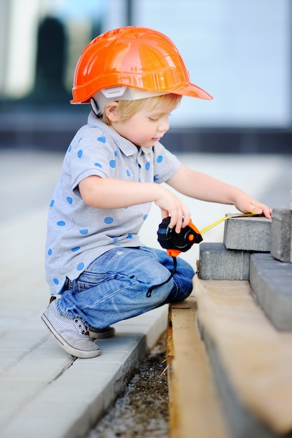 Portrait of cute little builder in hardhats with ruler working outdoors Premium Photo