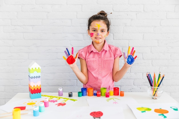 Portrait of cute little girl showing her painted hands standing against white brick wall Free Photo