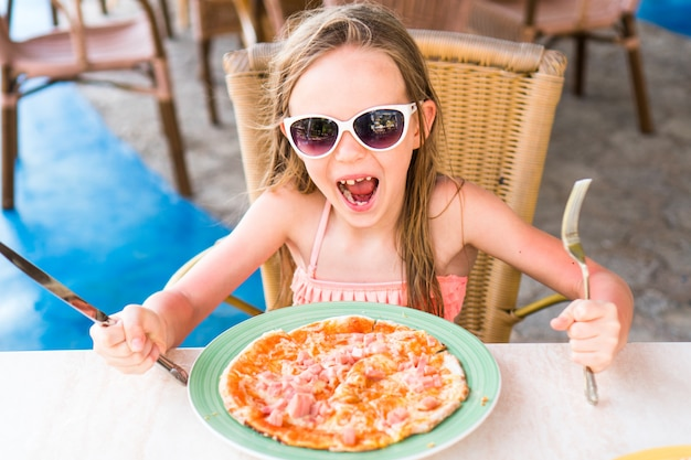Portrait of cute little girl sitting by dinner table and eating pizza Premium Photo