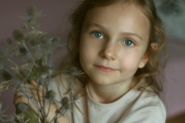 Portrait Of A Cute Little Girl With Curly Hair And Big Blue Eyes Sitting On A