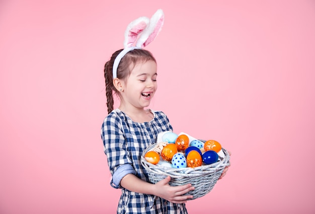 Portrait of a cute little girl with an easter egg basket on an isolated pink background. Free Photo