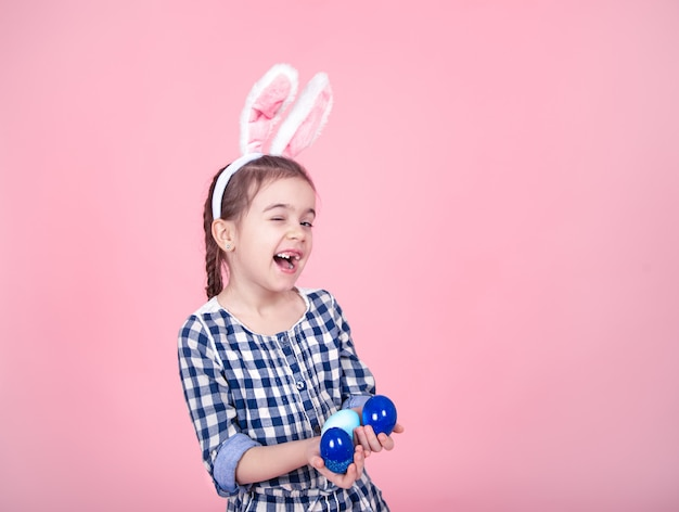 Portrait of a cute little girl with easter eggs on a pink background. Free Photo