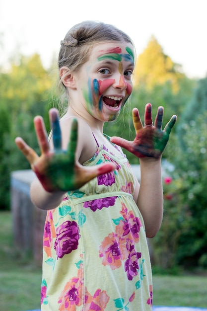 Portrait of a cute little girl with painted face and hands Premium Photo
