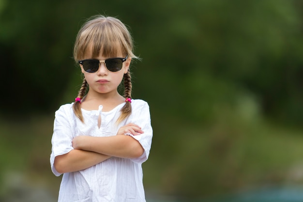 Portrait of cute pretty funny cool confident fashionable moody young blond preschool girl with blond braids in white dress Premium Photo