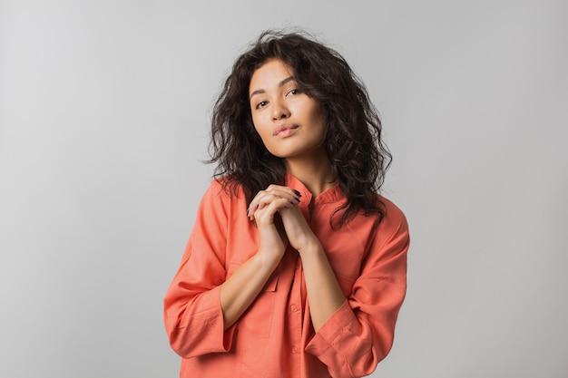 Ritratto di bella donna timida carina in camicia elegante arancione, capelli ricci, sorridente, tenendo le mani insieme, isolato Foto Gratuite