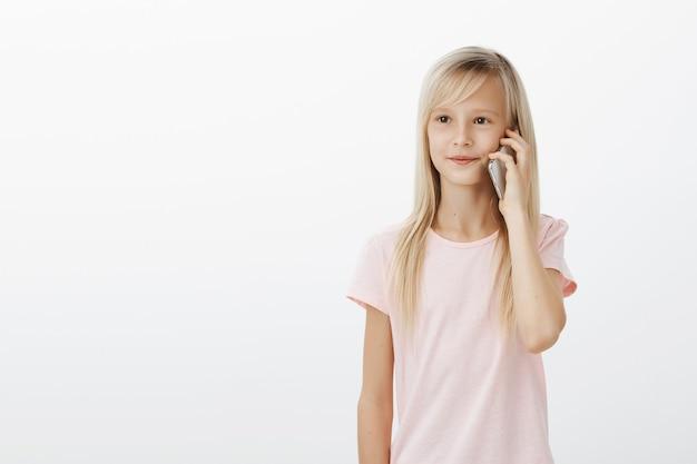 Ritratto di carina giovane figlia con capelli biondi, tenendo lo smartphone vicino all'orecchio e guardando da parte con espressione soddisfatta concentrata, parlando con il fratello Foto Gratuite
