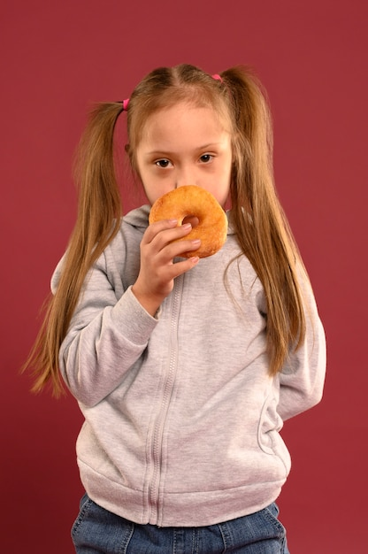 Portrait of cute young girl eating doughnut Free Photo