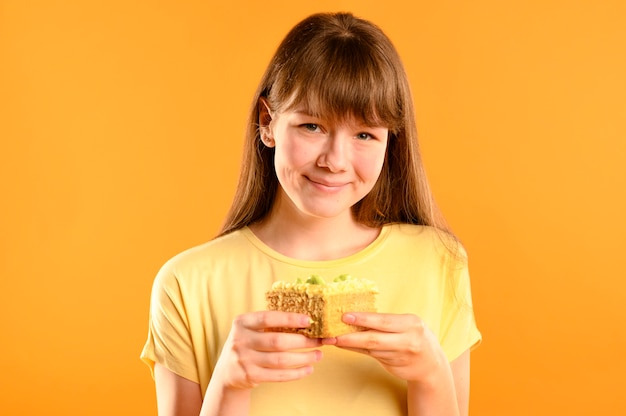 Portrait of cute young girl holding cake Free Photo