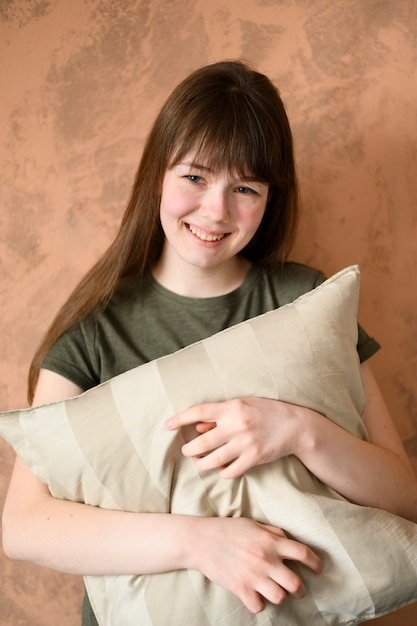 Portrait of cute young girl holding pillow Free Photo