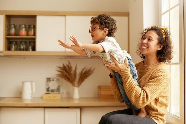 Ritratto di carino giovane donna latina in maglione seduto su wndowsill tenendo il suo figlio di due anni che sta raggiungendo le mani come se volasse. mamma felice e bambino che giocano nell'accogliente cucina interna Foto Gratuite