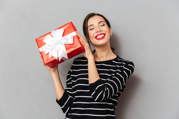 Portrait of a delighted woman holding gift box Free Photo