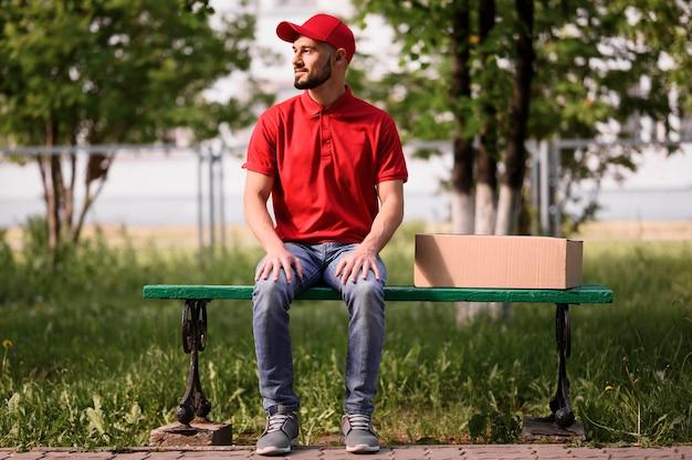 Ritratto di uomo di consegna seduto su una panchina Foto Gratuite