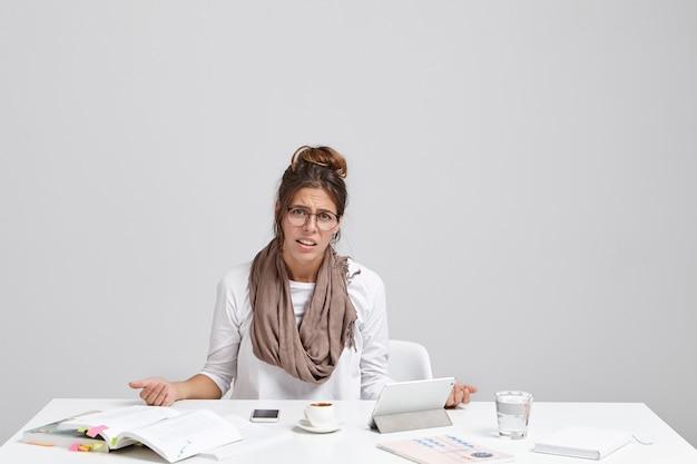 Ritratto di malcontento stanco giovane bella imprenditrice si siede alla scrivania in ufficio Foto Gratuite