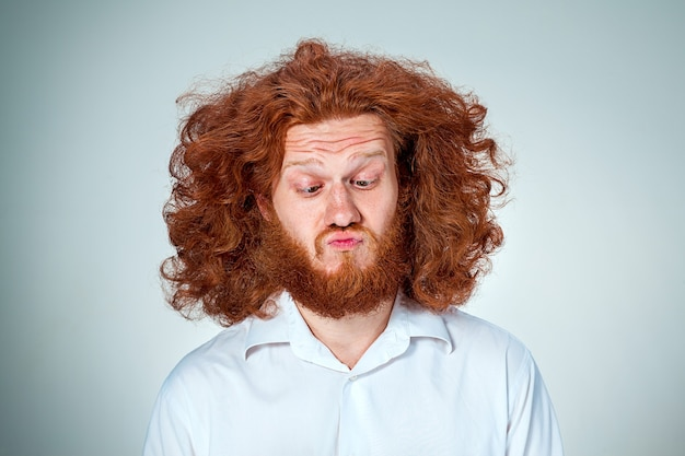 The portrait of disgusted man with long red hair Free Photo