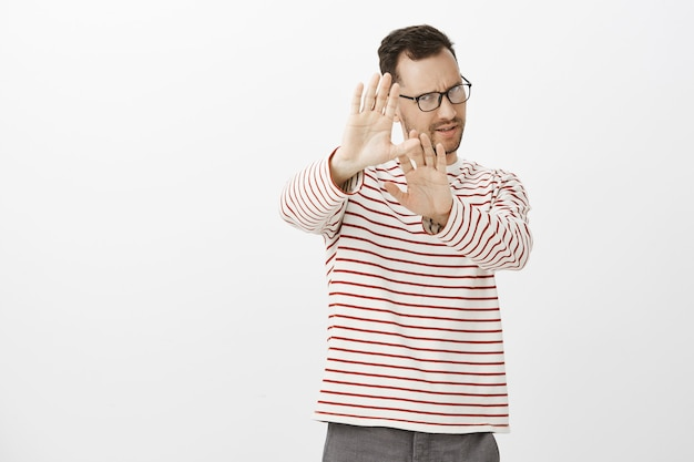 Ritratto di un uomo schizzinoso dispiaciuto con setole, che tira i palmi verso il gesto di no o stop, rifiuta o copre il viso da qualcosa di disgustoso, in piedi deluso e indifferente Foto Gratuite
