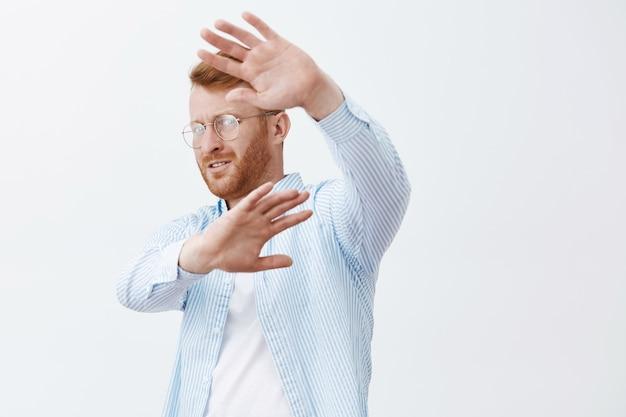 Ritratto del famoso imprenditore maschio scontento, turbato e preoccupato con i capelli rossi, voltandosi, coprendosi il viso con i palmi sollevati, cercando di nascondersi dai paparazzi sul muro grigio Foto Gratuite