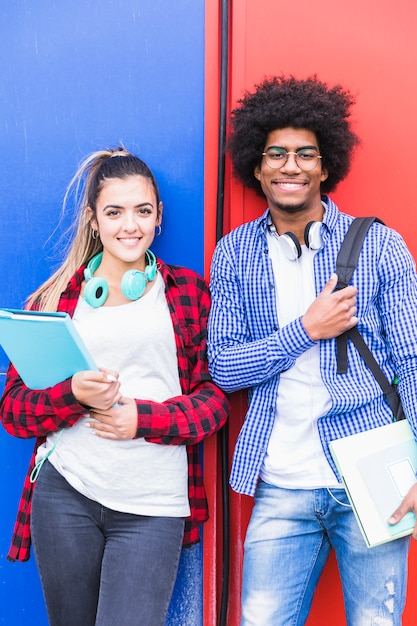 Portrait of diverse female and male student smiling to camera against wall Free Photo