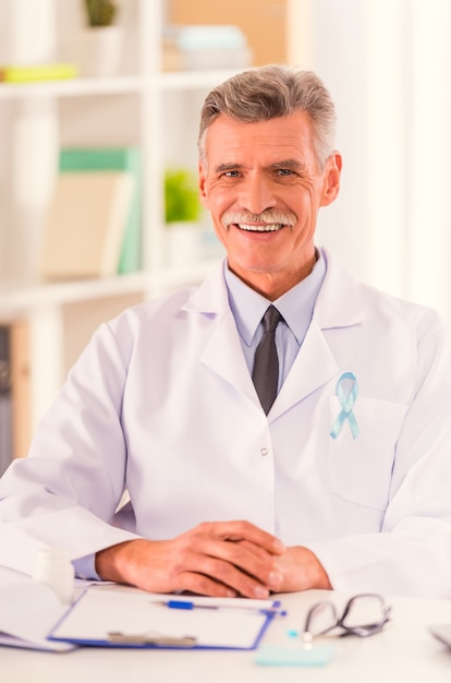 Portrait of doctor with blue ribbon sitting in his office. Premium Photo