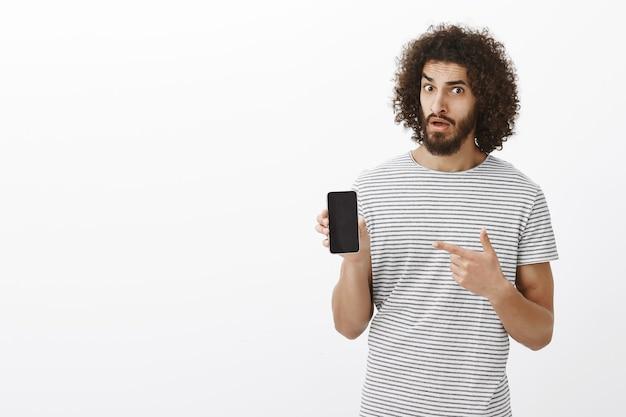 Ritratto del maschio attraente dubbioso incredulo con capelli ricci, che tiene smartphone e che indica con il dito indice al dispositivo Foto Gratuite