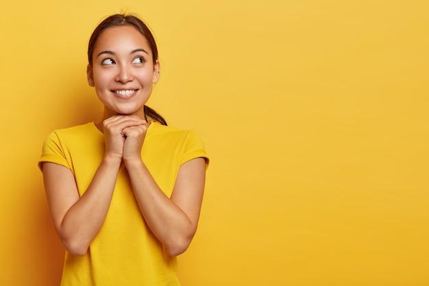 Ritratto di ragazza etnica soddisfatta sognante concentrata da parte con un sorriso felice, tiene le mani sotto il mento, guarda con espressione speranzosa, crede in meglio, indossa una maglietta gialla casual, sta dentro Foto Gratuite